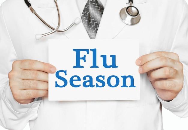 Doktor hält eine karte mit grippesaison