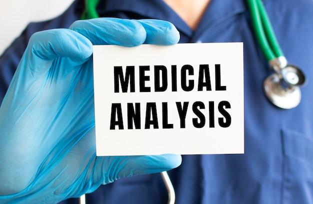 Doktor hält eine karte mit text medical analysis. medizinisches konzept.