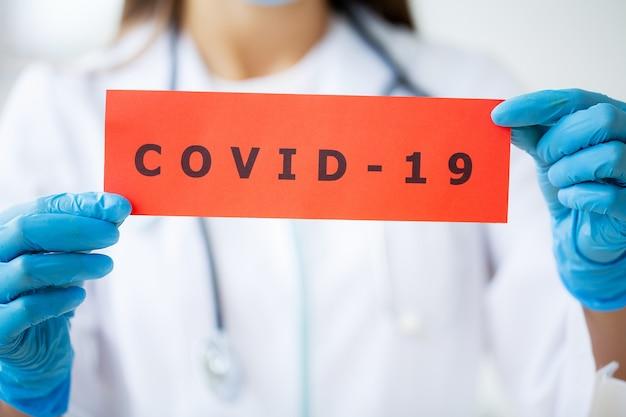 Doktor hält eine papierkarte mit text covid-19.