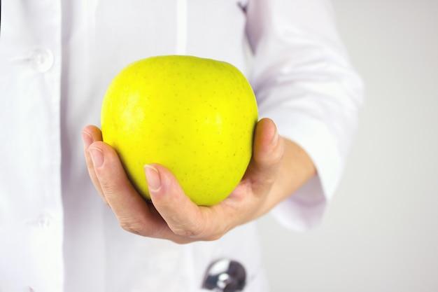 Doktor hält grünen apfel. großer grüner apfel in der hand des arztes. gesundheit in ihren händen