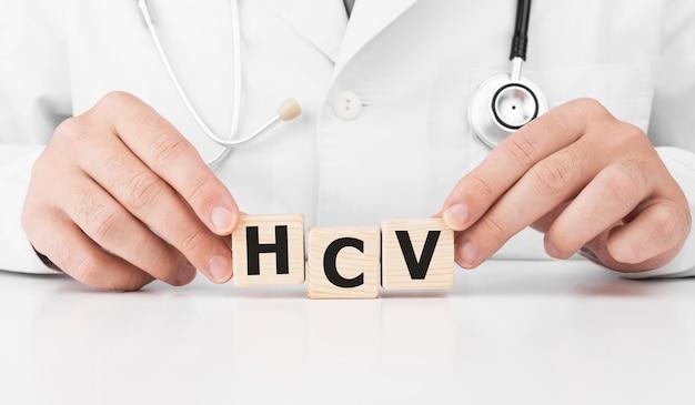 Doktor hält holzwürfel in seinen händen mit text hcv