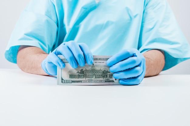 Doktor hält hundert dollarnoten. das konzept der korruption in der medizin