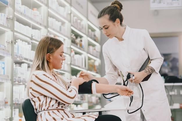 Doktor hält zifferblatt, während der druck der frau gemessen wird. frau in weißer uniform.
