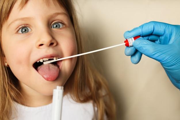 Doktor hände in schutzhandschuhen, die coronavirus-testabstrich in kindermund setzen.