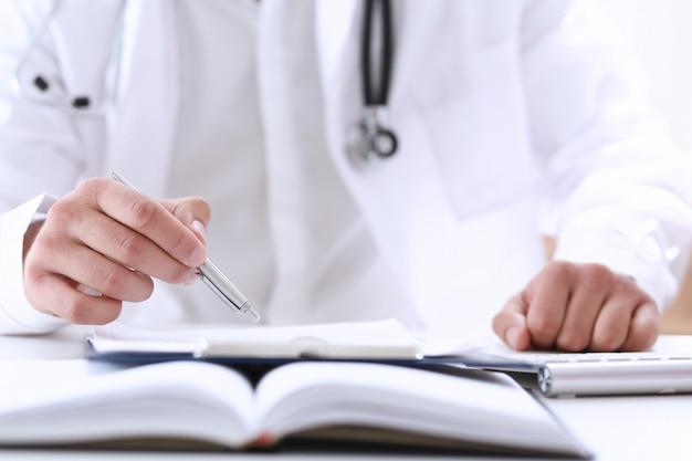 Doktor hand halten silberstift füllung patientengeschichte liste