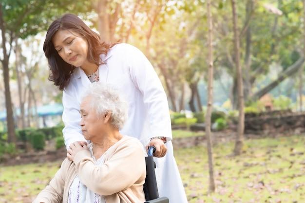 Doktor helfen und pflegen asiatische ältere frau patient, die auf rollstuhl am park sitzt.