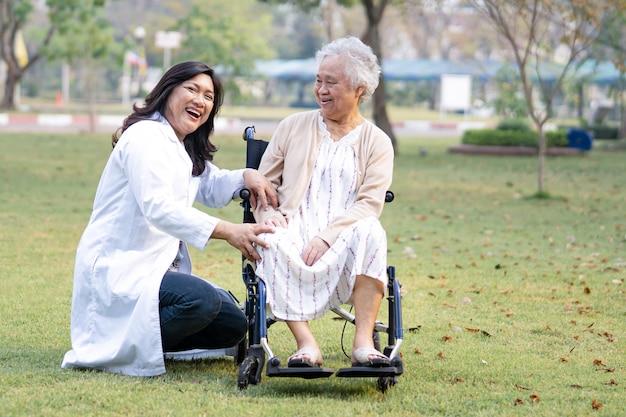 Doktor helfen und pflegen asiatische ältere frau patient, die auf rollstuhl im park sitzt
