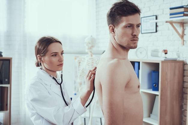 Doktor hört auf lungen mit stethoskop