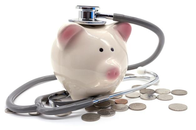 Doktor holding stethoscope zum sparschwein