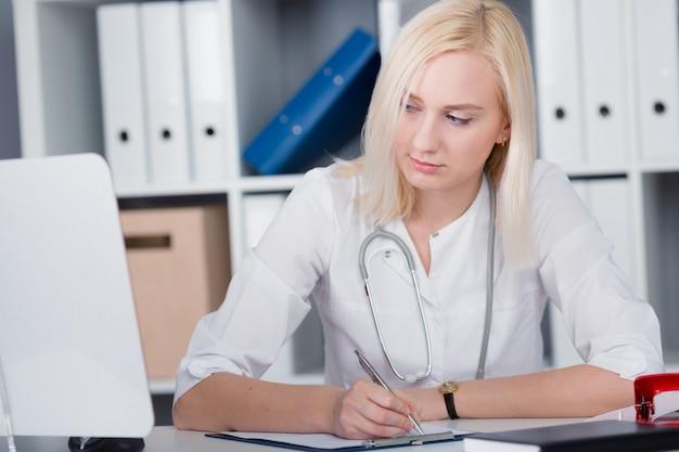 Doktor im büro macht eine aufzeichnung im empfangsprotokoll
