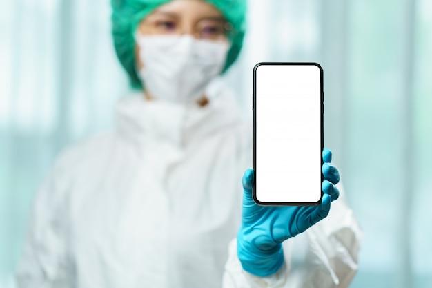 Doktor im hazmat-anzug (psa), der ein smartphone mit leerem weißen bildschirm für text hält. coronavirus, covid-19-ausbruchskonzept.