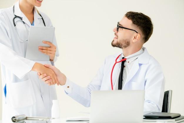 Doktor im krankenhaus rüttelt hand mit einem anderen doktor