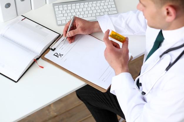Doktor im mantel hält eine flasche mit pillen