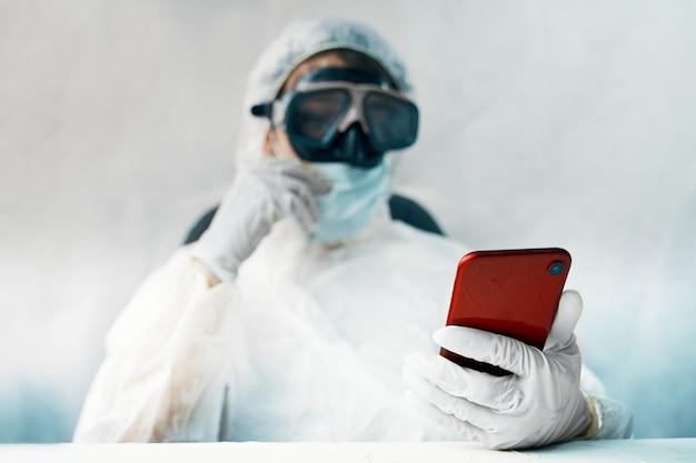 Doktor im schutzanzug mit smartphone