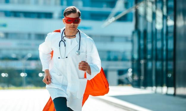 Doktor im superhelden-umhang, der selbstbewusst nach vorne schreitet