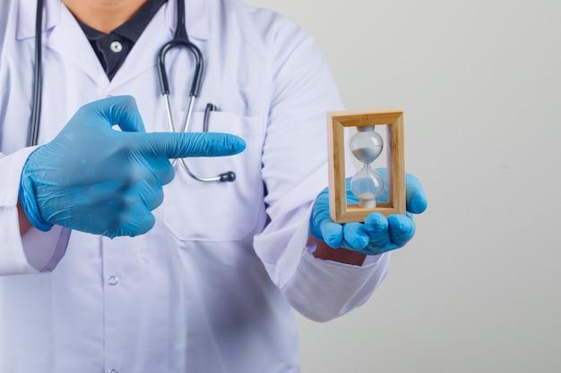 Doktor im weißen kittel, der sanduhr in seiner hand zeigt