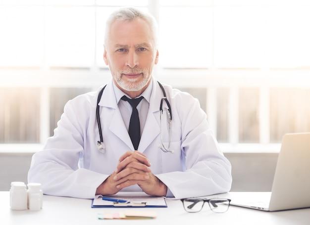Doktor im weißen kittel hält hände zusammen
