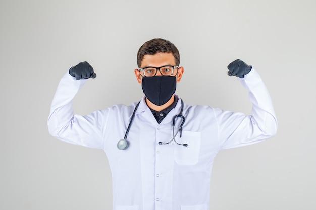 Doktor im weißen kittel mit stethoskop, das seinen bizeps zeigt und kraftvoll aussieht