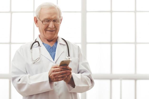 Doktor im weißen medizinischen mantel benutzt einen smartphone.