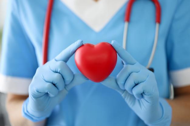 Doktor in blauem anzug, handschuhen und mit rotem stethoskop halten symbol.