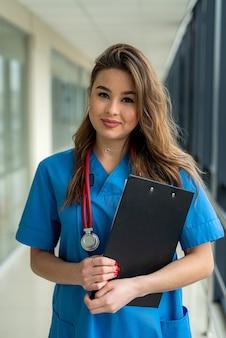 Doktor in blauer medizinischer form mit einem stethoskop, mit einem klemmbrett in der hand, das im krankenhaus steht