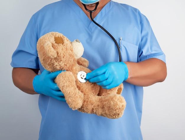 Doktor in blauer uniform und weißen latexhandschuhen hält einen braunen teddybär,