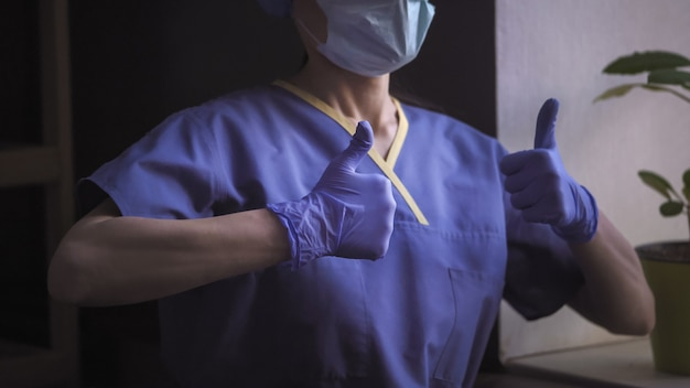 Doktor in blauer uniform zeigt daumen hoch