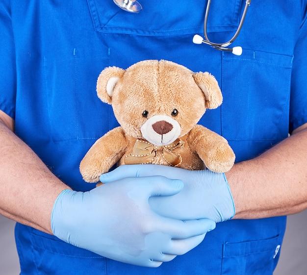 Doktor in den blauen uniform- und latexhandschuhen, die einen braunen teddybären halten