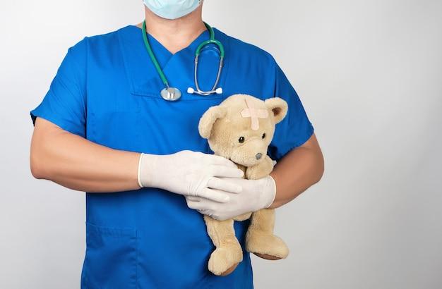 Doktor in den blauen uniform- und weißlatexhandschuhen, die einen braunen teddybären halten