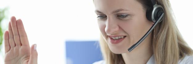 Doktor in den kopfhörern mit dem mikrofon, das hand-laptop-bildschirm winkt