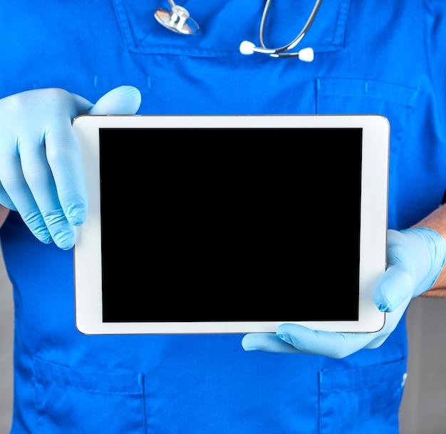 Doktor in den sterilen handschuhen der blauen uniform und des latex, die eine elektronische tablette mit einem leeren schwarzen schirm halten