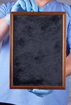 Doktor in den sterilen handschuhen der blauen uniform und des latex, die einen leeren schwarzen rahmenhintergrund halten