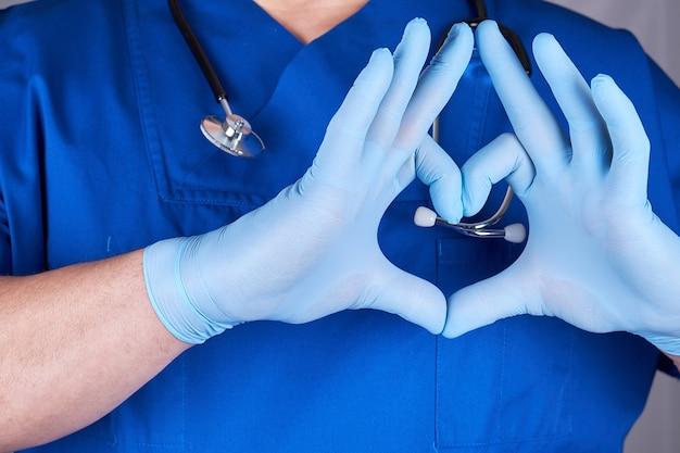 Doktor in der blauen uniform und in den alten latexhandschuhen, die herz zeigen, gestikulieren