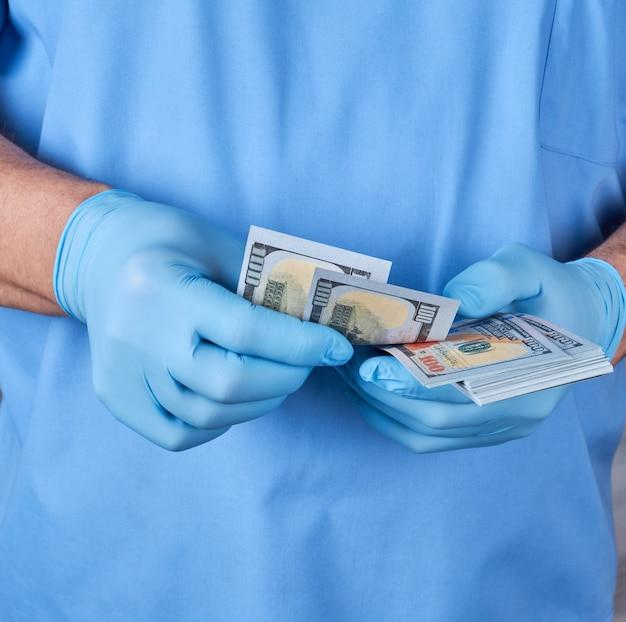 Doktor in der blauen uniform und in den handschuhen zählt geld nach