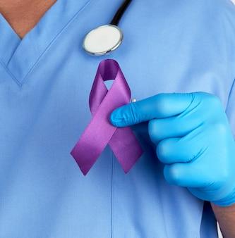 Doktor in der blauen uniform und in den latexhandschuhen hält ein purpurrotes band