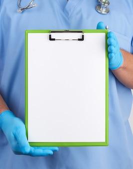 Doktor in der blauen uniform und in den latexhandschuhen hält einen blauen halter für blätter papier