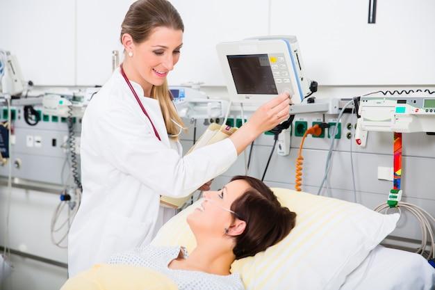 Doktor in der intensiven medizinischen behandlung, die ergebnisse des frauenpatienten überprüft