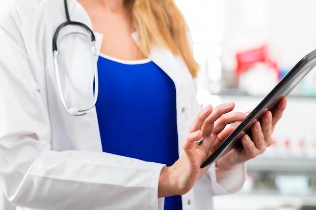 Doktor in der klinik, die digitale datei auf tablet-computer liest