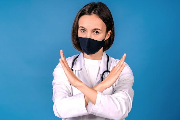Doktor in der schutzmaske, die stoppgeste auf blauer wand zeigt. verhindern sie die ausbreitung von coronavirus. ärztin hände, die gekreuztes stoppschild zeigen. arzt trägt maske stoppt das coronavirus bei infektionen