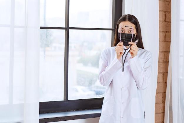 Doktor in der schwarzen maske mit einem stethoskop, das am fenster steht.