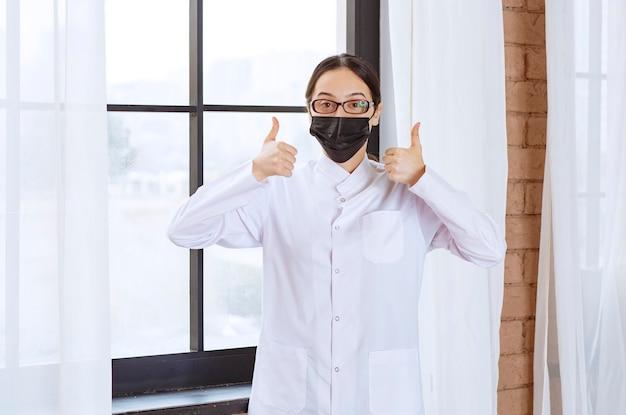 Doktor in der schwarzen maske und in den brillen, die am fenster stehen und genusszeichen zeigen.