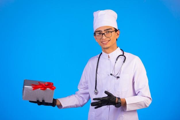 Doktor in der weißen medizinischen uniform, die eine geschenkbox hält und zur kamera schaut.