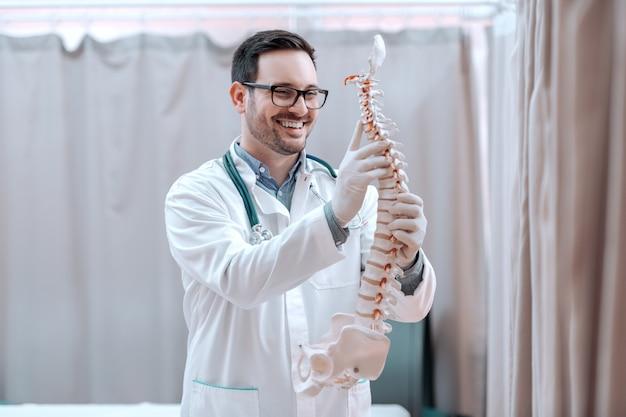 Doktor in der weißen uniform, die rückenmodell hält.