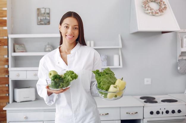 Doktor in einer küche mit gemüse