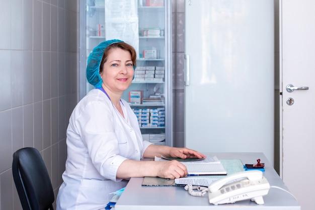 Doktor in einer medizinischen mütze sitzt am tisch und lächelt