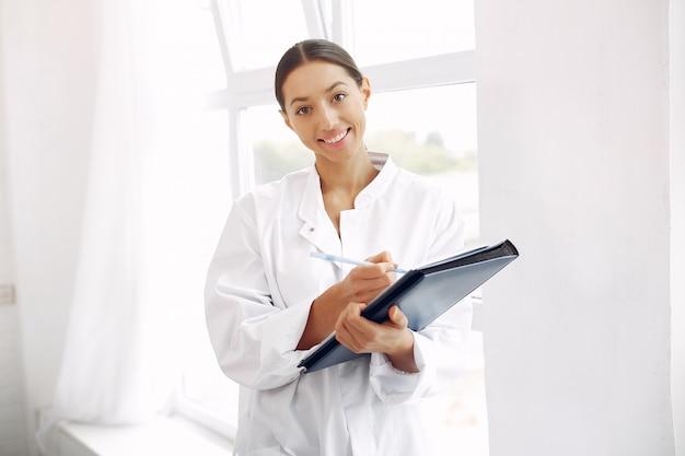 Doktor in einer uniform, die auf weiß steht