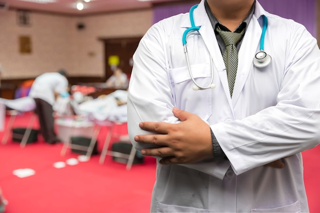 Doktor in gewanduniform mit stethoskop, das im blutspenderraum steht