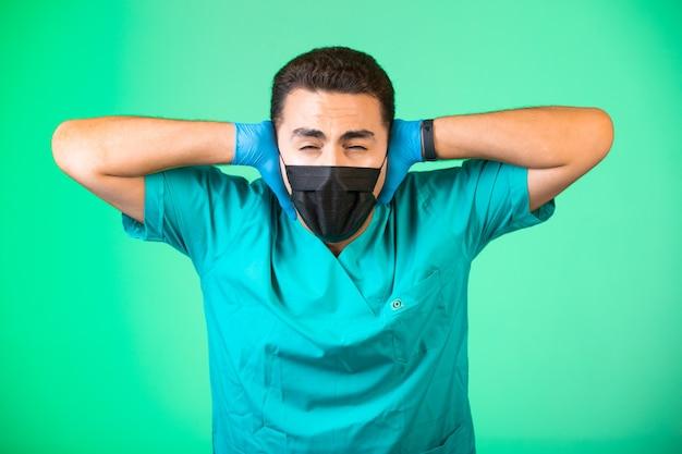 Doktor in grüner uniform und gesichtsmaske, die seine ohren und augen schließt.
