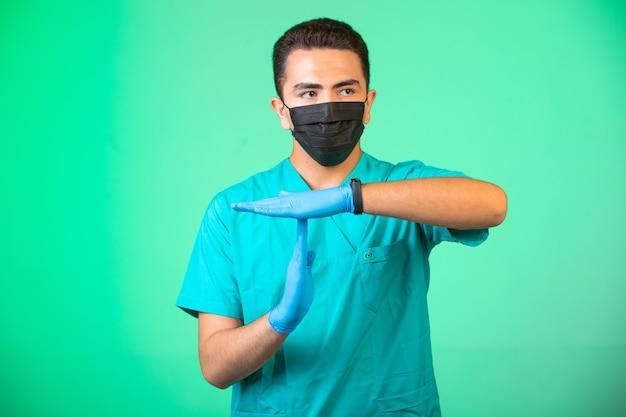 Doktor in grüner uniform und gesichtsmaske macht handgesten, um die leute verständlich zu machen.