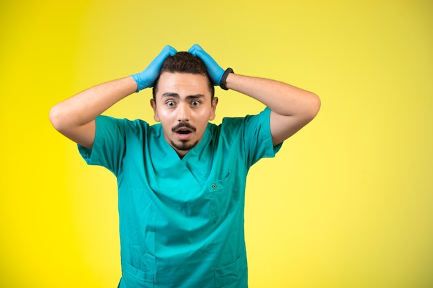 Doktor in grüner uniform und handmaske frustriert und verwirrt.
